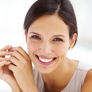 Woman smiling about the cost of dentistry image